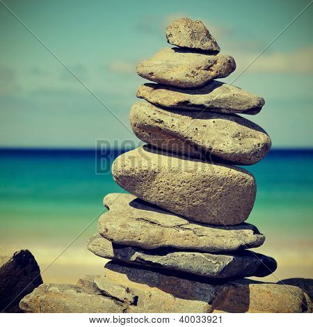 closeup of a stack of stones on a beach, with a retro effect