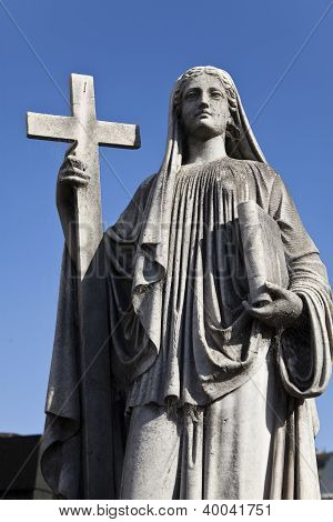 Sculpture Of A Woman Holding The Cross And One Book