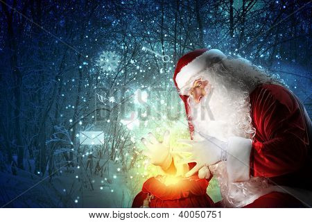 Santa with beard and red hat holding and looking into the sack