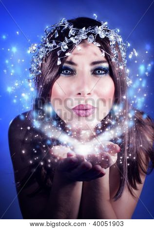Photo of beautiful Christmas fairy blowing snow, sexy woman holding snowflake, stunning female  isolated on blue background, winter holiday magic light in hands, happy girl kiss, fashion, party makeup