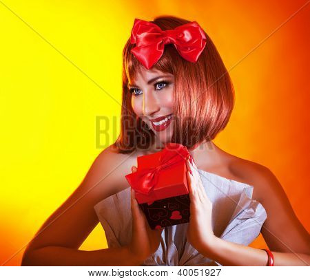 Picture of pretty woman with red bow in hair holding gift box in hands, gorgeous female with red hair isolated on yellow background, attractive girl wearing stylish festive dress, New Year party