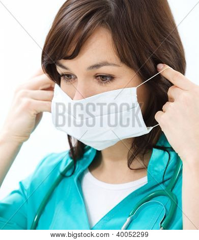 Portrait of a woman in doctor uniform wearing surgical mask
