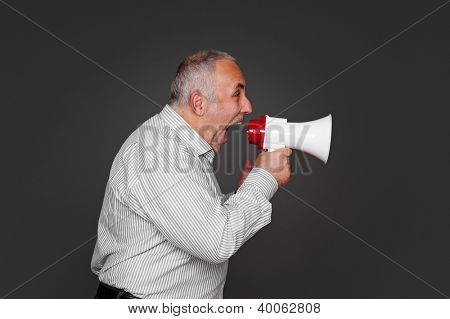 sideview of senior man shouting using megaphone over grey background
