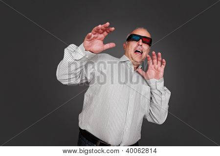 emotional senior man in stereo glasses watching horror movie. studio shot over grey background
