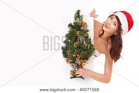 Santa woman with christmas tree peek behind the white blank board