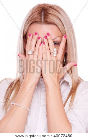 Adult blonde playing hide-and-seek covering the face with his hands and peek through fingers, isolated on white