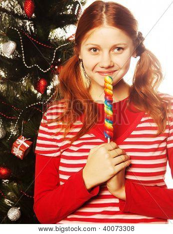 Hübsche junge Redhair Frau holding Lolly pop. Weihnachtsbaum.