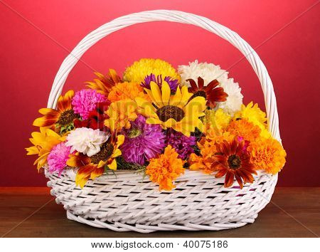 Beautiful bouquet of bright flowers in white basket on wooden table on pink background