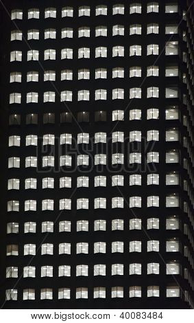 window of the night empty multi-storey skycraper building of glass and steel office lighting and with no people within
