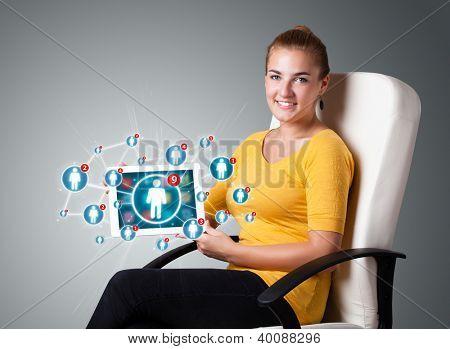 Tableta de celebración hermosa joven con los iconos de redes sociales