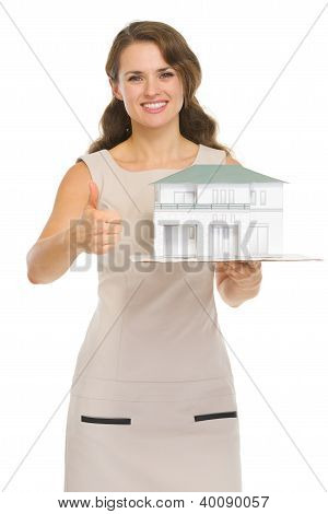 Happy Woman Landlord With Scale Model Of House Showing Thumbs Up