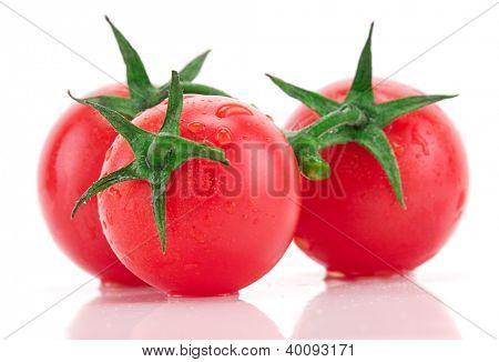 Wet fresh tomatoes isolated on white background