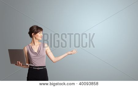 attractive young woman holding a laptop with copy space