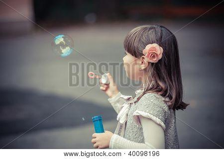 Portrait of funny lovely little girl blowing soap bubble