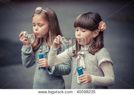 Portrait of funny lovely little girls blowing soap bubble