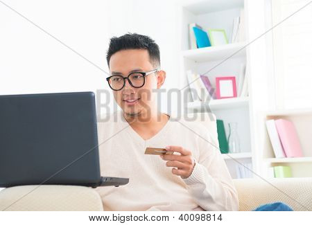 Southeast Asian male holding credit card online shopping at home