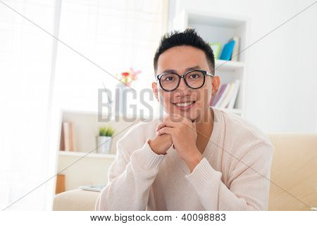 Portrait of a smiling southeast Asian male sitting on sofa at home