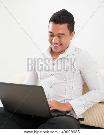 Southeast Asian man sitting on floor, browsing internet.