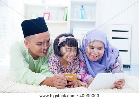 Southeast Asian family online shopping with credit card at home. Muslim family living lifestyle.