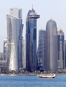 image of qatar  - A dhow passes beneath some of the most massive buildings in Doha - JPG