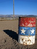 picture of barrel racing  - An old painted barrel in a rural rodeo arena - JPG