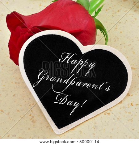 sentence happy grandparents day written with chalk on a heart-shaped blackboard with a red rose in the background