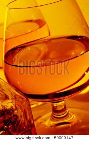 closeup of some cognac glasses with liquor and a vintage glass liquor bottle