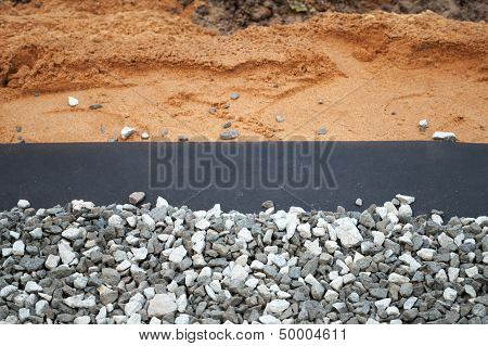 Geotextile With Gray Gravel Above Sandy Backdrop