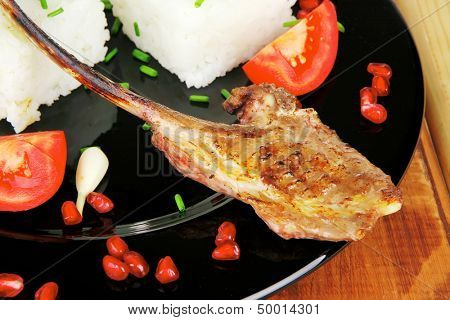 meat portion: barbecued ribs served with rice and tomatoes on black over wood