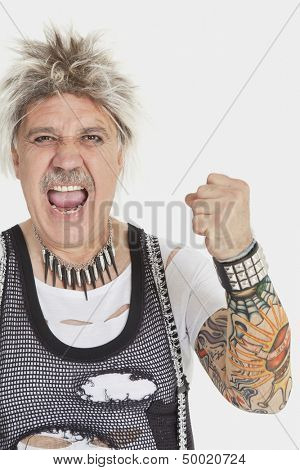 Portrait of senior male punk screaming with clenched fist over gray background