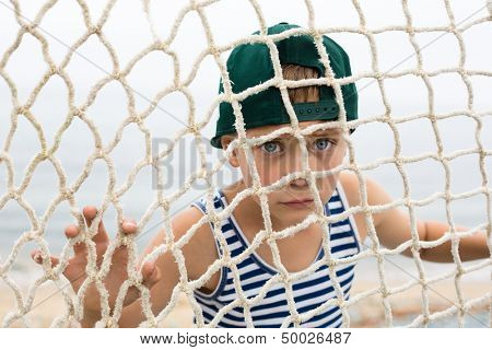 Fisher boy with the piercing eyes looking through the fishing net. Oceanside.