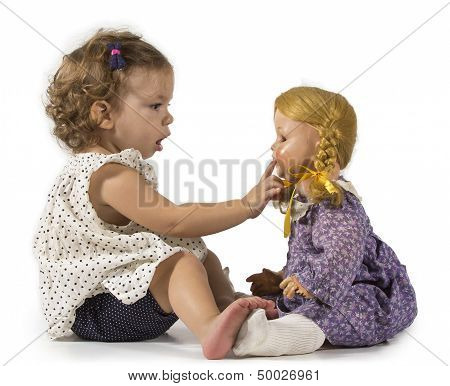 Baby girl playing with her doll