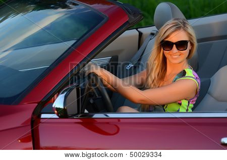Beautiful woman at wheel the red car