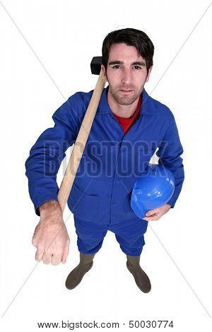 Man posing with sledge-hammer over shoulder