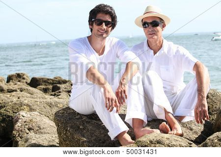 father and son posing at sea resort