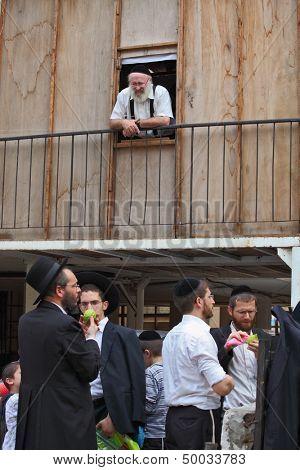 Bnei Brak - September 22: Picturesque scene: A group of young religious Jews in black velvet skullcaps on the market to choose citron Sukkot. September 22, 2010 in Bnei Brak, Israel