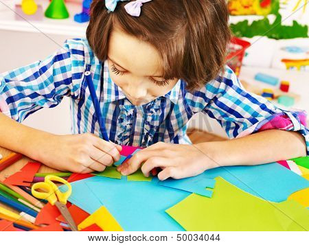 Little girl with  scissor  at school. Education.