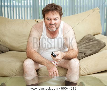 Unemployed man sitting home watching TV, bored and discouraged.
