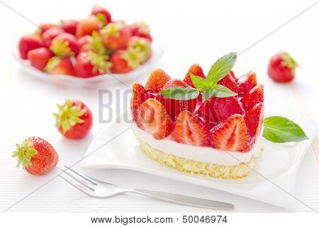 Small strawberry cake or piece with strawberries in the background.