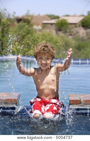 Boy Splashing In A Pool