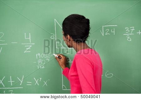 Side view of young African American female teacher solving mathematics on board in classroom