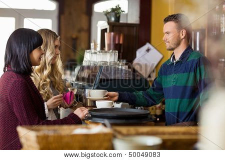 Side view of bartender serving coffee to women in coffeeshop