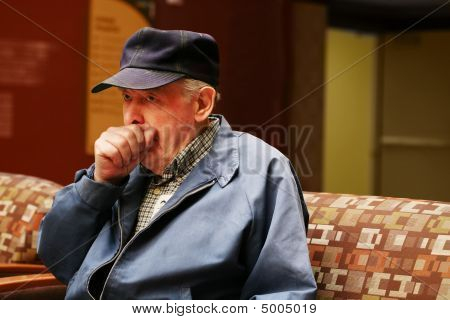 Senior Man Sitting In Waiting Room Coughing