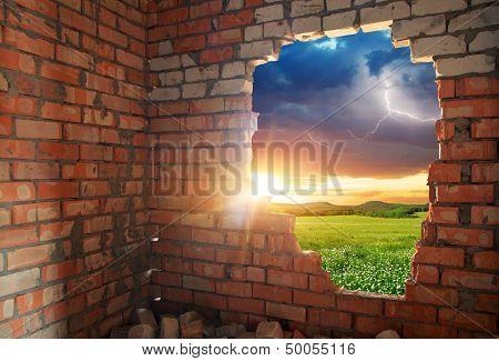 Broken bricks wall and landscape. Conceptual composition.