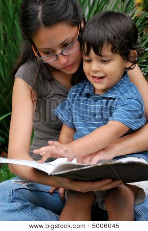 Young Hispanic Mother Reading To Her Son