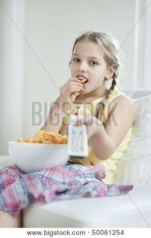 Little girl watching TV as she eats wheel shape snack pellets