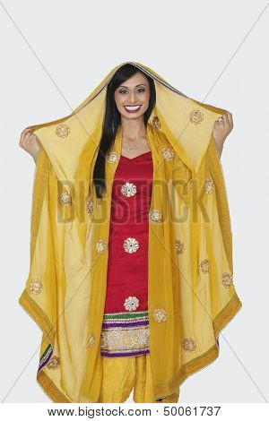 Portrait of beautiful Indian woman in salwar kameez standing over gray background