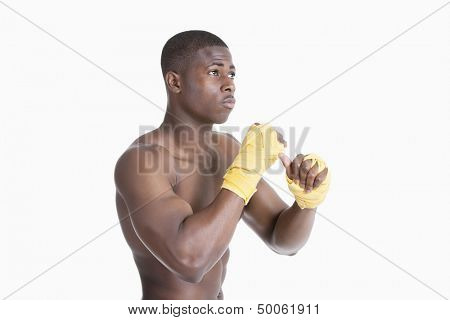 Shirtless African American kickboxer over gray background