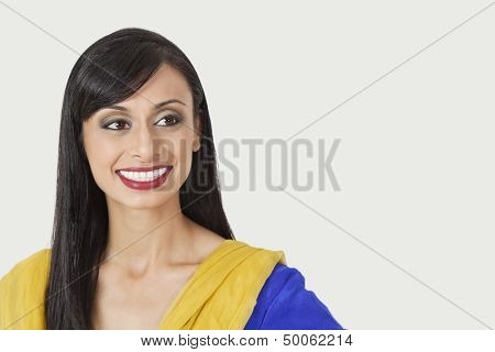Beautiful Indian woman looking sideways over gray background