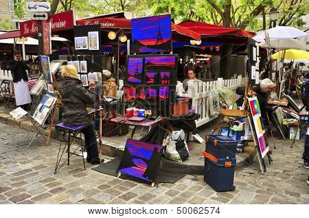 PARIS, FRANCE - MAY 14: Artists in Place du Tertre on May 14, 2013 in Paris, France. Many artists set up their easels each day for the tourists in this famous and picturesque square in Montmartre